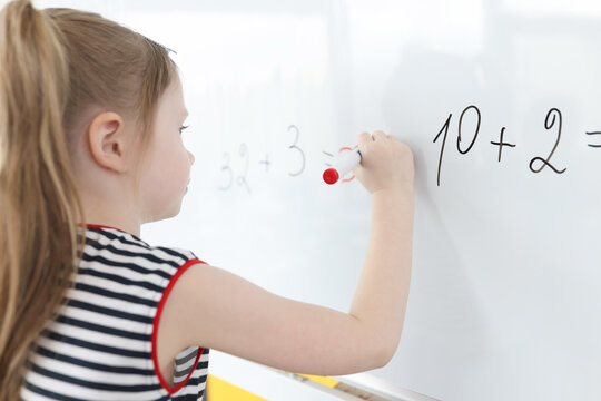 Little girl writes math examples on white board