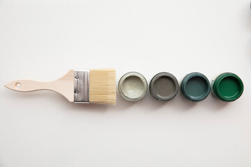 Obraz Overhead view of a DIY paint brush with trendy green sample paint pots - fototapety do salonu