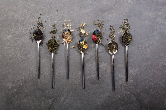 Different types of dry tea leaves set on a table