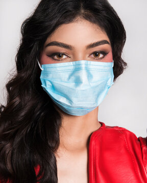 Portrait Of Beautiful Young Woman Wearing Mask Over White Background