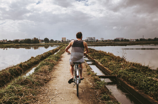 Rear View Of Man Riding Bicycle On Water Against Sky