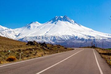 Road Leading Towards Snowcapped Mountain Against Blue Sky Fototapete