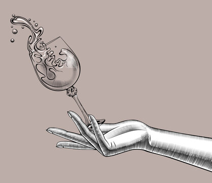 Female hand with a falling glass with splashed wine. Vintage engraving stylized drawing