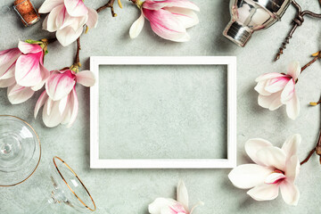 Photo frame mock up with space for text, beautiful spring magnolia flowers, Cocktail Shaker and glasses on grey stone background. Flat lay, top view, copy space