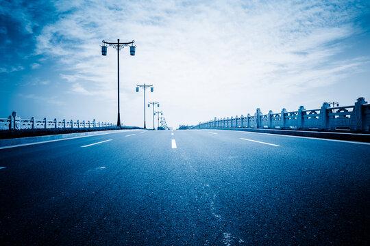 Road Leading Towards Bridge Against Sky In City