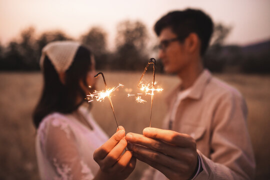Couple Holding Sparkler While Standing On Field
