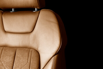 Fototapeta Modern luxury car brown leather with alcantara interior. Part of orange leather car seat details with white stitching. Interior of prestige car. Perforated leather seats isolated. Perforated leather.