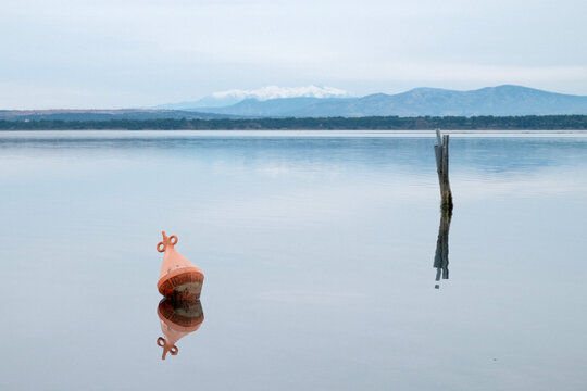 A Buoy And Un Piece Of Wood Reflecting On A Lake With Mountains In The Background