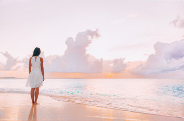 Fototapeta Paradise beach elegant woman walking relaxing watching pink sunset on idyllic travel Caribbean vacation destination. Clouds and ocean serene scenery relaxation.