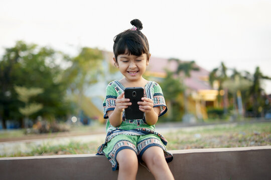 Girl Using Phone While Sitting On Retaining Wall Against Sky