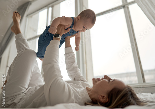 Home portrait of a baby boy with mother on the bed. Mom holding and kissing her child. Mother's day concept. High quality photo