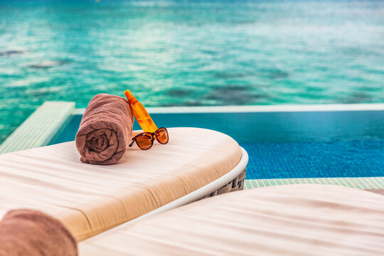 Hotel infinity swimming pool background sun loungers background for luxury relaxing holidays in Caribbean destination. Tropics lifestyle sunblock and sunglasses solar protection.