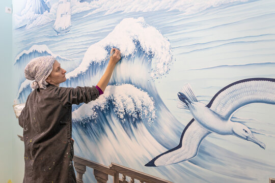 Mature Woman Artist Draws A Mural On A Marine Theme