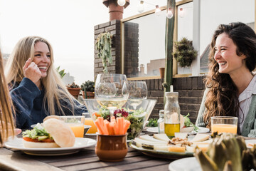 Fototapeta Happy friends eating vegan food with wine outdoors in summer sunset at patio restaurant - Main focus right woman face obraz