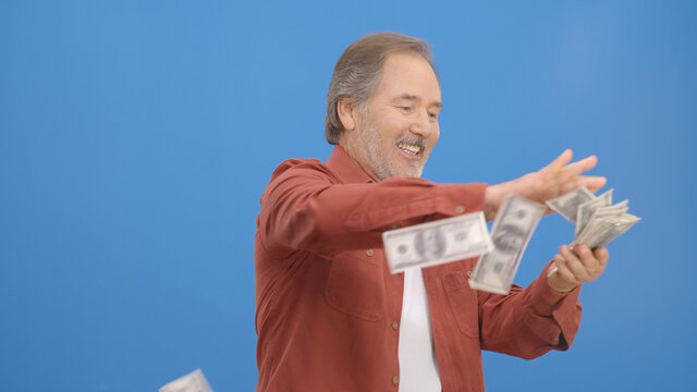 Old man with beard in front of a blue background who is cheerfully gesturing while handing out money. Concept of to pour money without thinking. It makes it rain by throwing money into the air.