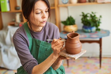 Woman potter makes a jug of clay, draws a pattern on the product