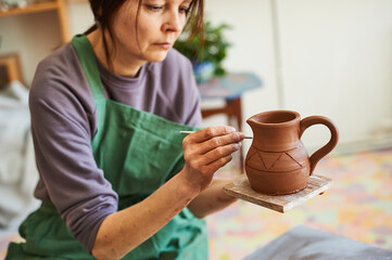 woman potter applies a pattern with a tool on the surface of an earthen jug.
