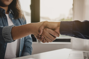 Successful young asian woman, man  partnership, team handshake together at office after project done, good deal. .Happy business people, worker meeting, shaking hands concept..