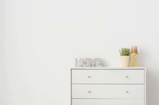Modern chest of drawers near light wall in room