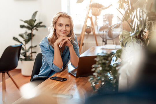 Thoughtful young woman poses in office room with laptop at table