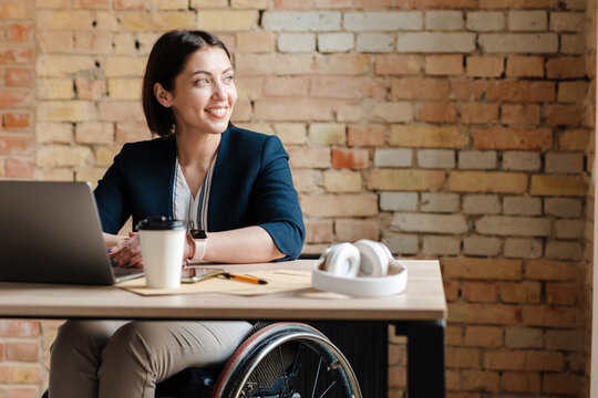 White smiling woman in wheelchair working with laptop at office