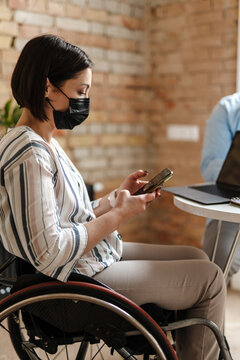 White young woman wearing face mask in wheelchair using mobile phone