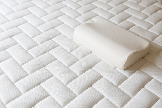 Close up shot of white orthopedic pillow and mattress pattern with a lot of copy space for text. Hypoallergenic foam matress for proper spinal alingment and pressure point relief. Background.
