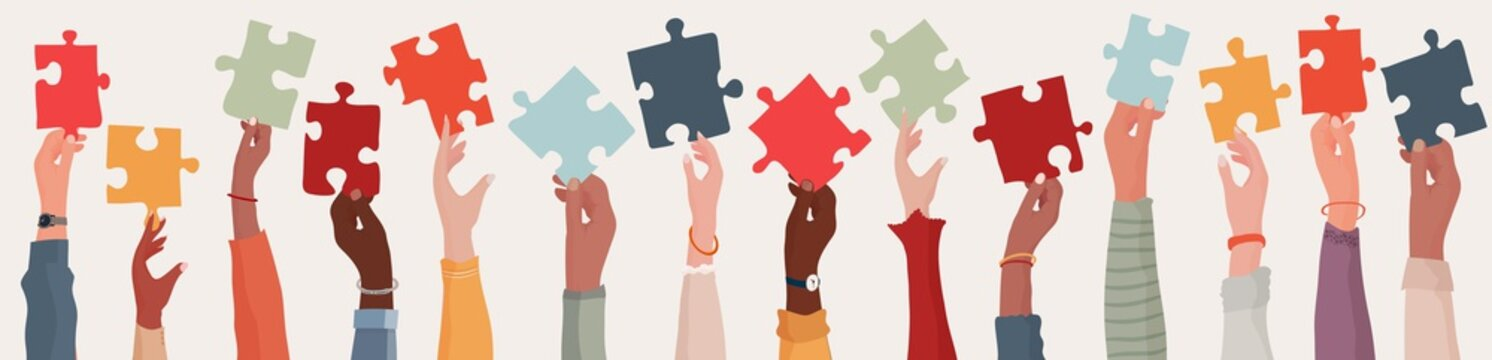 Group of multi-ethnic business people with raised arms holding a piece of jigsaw. Colleagues of diverse races and culture. Cooperate and collaborate. Concept of teamwork and success