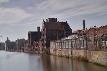 Fototapeta Stare po przemysłowe budynki nad brzegiem rzeki w mieście Szczecin