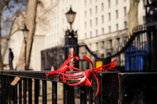 Close-up Of Red Tied To Metal Railing Against Buildings In City