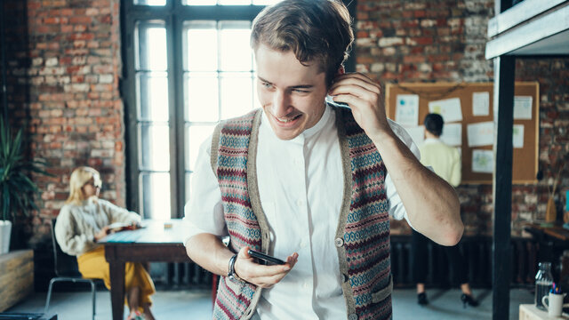 Portrait of handsome young man in loft office using smartphone