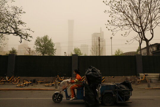 Sanitation worker rides a vehicle past buildings shrouded in sand and dust amid a duststorm in Beijing