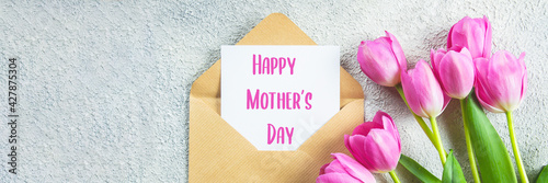 Mother's day Concept. Pink tulips, greeting card on concrete background. Flat lay. Banner image