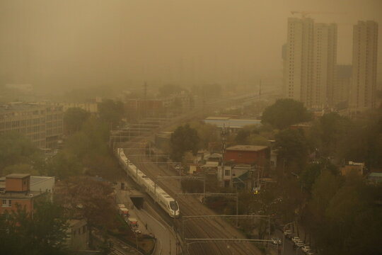 High speed train travels past buildings shrouded in sand and dust amid a duststorm in Beijing