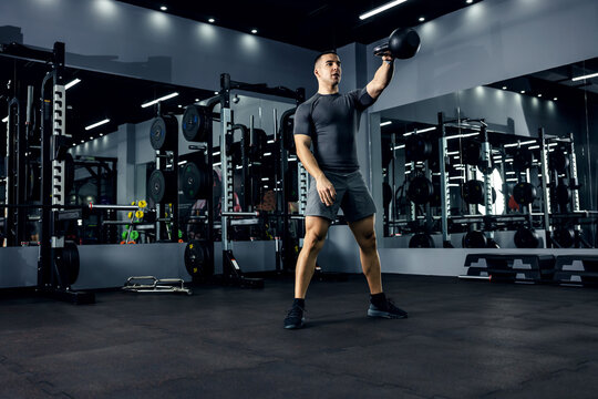 A muscular man in a gray T-shirt is doing a cross-fit workout in a gym with low lighting. He is in a squat position and does a dead lift with a kettle bell that he lifted over his head. Power boost