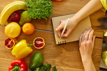 Woman planning, writing weekly meals on a meal planner note or diet plan