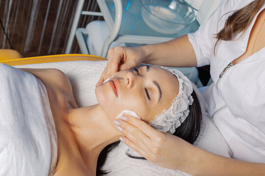 Professional beautician woman wipes face with cotton pads to client.