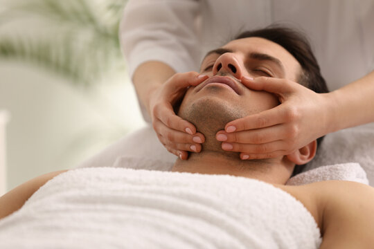 Man receiving facial massage in beauty salon