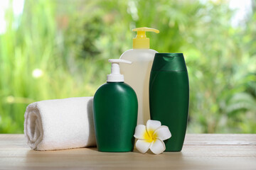 Wall Mural - Different shower gel bottles with towel and plumeria flower on wooden table