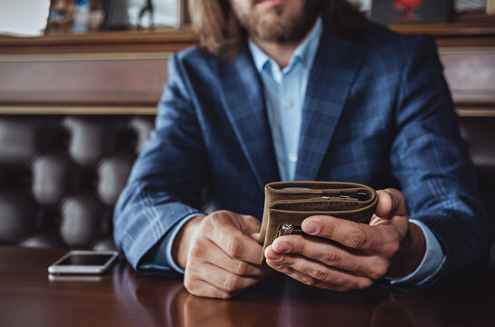 A business man at the table holds a wallet in his hands. Horizontal orientation, no face