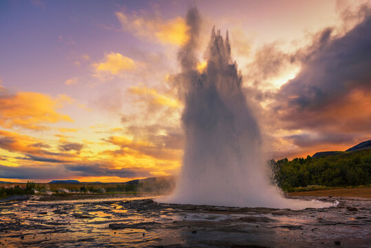 Eruption of Strokkur geyser in Iceland at sunset