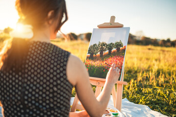 Fototapeta Happy girl painting outdoors on canvas at seunset obraz