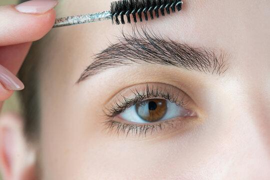 Eyebrow shaping. Beautiful woman gets eyebrow correction procedure. Close up. Female eye with perfect shape eyebrows. Perfect eyebrows.