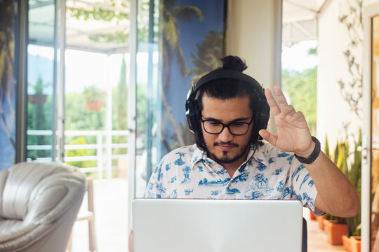 Young Latino male college student with headset, raising his hand in class in virtual classroom in front of laptop by zoom. video conference call at home.