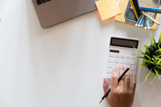 Top view hand of accountant using calculator on workplace with copy space, calculator and plant potted on white desk background, Accounting workplace concept