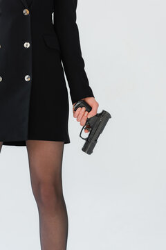 cropped view of stylish woman holding gun isolated on grey