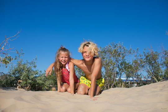 Boy and girl posing on sand beach with shrubs. Blue sky. Copy space.