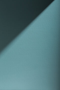 An aegean teal painted wall with shadows.