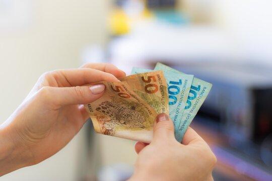 mão com dinheiro real brasileiro