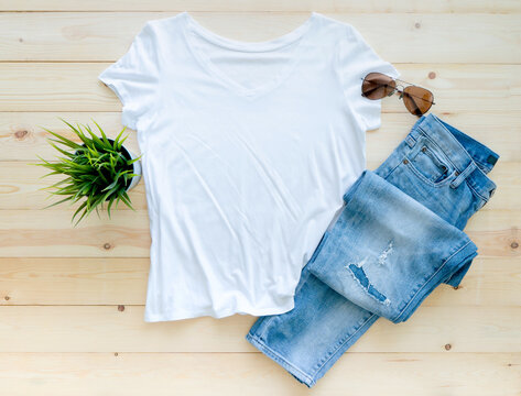 flat lay, White tshirt mockup jeans and sunglasses on brown wooden background. Template,